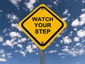 Watch your step sign warning with blue sky and cloudscape background Royalty Free Stock Image