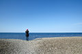 Watching blue sea woman from a coast of gravel Stock Photo