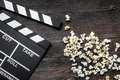Watching the film. Movie clapperboard and popcorn on wooden table background top view copyspace