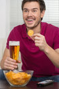 Watching a game. Cheerful young men drinking beer and eating snacks while watching TV Royalty Free Stock Photo