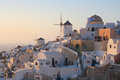 Watching sunset from oia tourists the as every summer evening by the popular kastro walls in santorini island greece Royalty Free Stock Photography