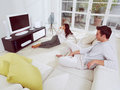 Watching television together happy mature couple sitting on couch and Stock Photography