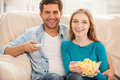 Watching tv together beautiful young couple sitting on the couch and Royalty Free Stock Photo