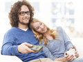 Watching tv together happy young couple relaxing at home and television Stock Photography