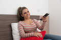 Watching tv and using remote control beautiful young woman television sitting on bed with the in her hand Stock Images
