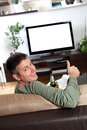 Watching tv young man relaxing and enjoying at home Royalty Free Stock Photography