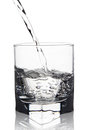 Water with air bubbles pouring into glass with its reflection, c Royalty Free Stock Photo