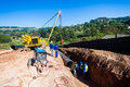 Water aqueduct pipeline crane installation new construction and trench between reservoirs outside durban south africa Stock Image
