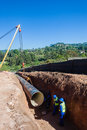 Water aqueduct pipeline rigging installation new construction and trench between reservoirs outside durban south africa Royalty Free Stock Image