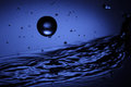 Water ball single splashing on a blue liquid background Royalty Free Stock Photography