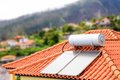 Water boiler with solar panels on roof of house Royalty Free Stock Photo