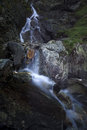 Water cascade stream flowing over rocks covered with moss Royalty Free Stock Photo