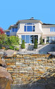 Water cascades over a manmade waterfall with the gorgeous new home as the backdrop Stock Photo