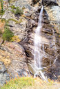 Water cascading over rocks, waterfall and autumn colors in the mountains, yellow and red trees Royalty Free Stock Photo