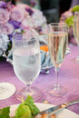 Water and champagne on wedding table glasses of cold sparkling banquet with pink purple flowers Royalty Free Stock Photos
