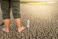 Water crisis, man on cracked earth near drying water. Royalty Free Stock Photo