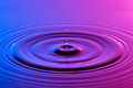 Water drop close up with concentric ripples colourful blue and p Royalty Free Stock Photo