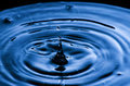 Water drop making a splash and ripple effect Royalty Free Stock Photo