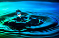Water drop and ripples shot on nice blue green turquoise background Royalty Free Stock Photo