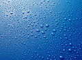Water drops beaded on blue metallic surface Royalty Free Stock Photo