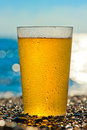 Water drops on a glass of cold beer on the beach Royalty Free Stock Photo