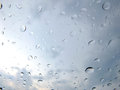 Water drops on a window pane of with cloudy sky in the background Stock Photography