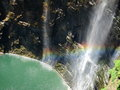 Water fall and rainbow there is a in the under the sun light the pond looks green clear Royalty Free Stock Photography