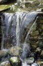 Water falling over stone wall in garden setting Royalty Free Stock Photo