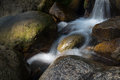 Water flowing and falling off large rocks clear around the Stock Image