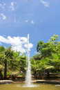 Water fountain in a small pond against a blue sky Stock Photo