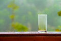 Water glass and flower pot on the wooden deck. Royalty Free Stock Photo