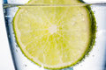 Water glass and lime a of fresh drinking a mineral as a thirst quencher Stock Image