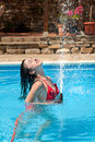 Water hose fun summer of a young woman playing with a in the swimming pool Stock Photo