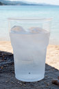 Water with ice cold in the glass cubes on the sandy beach sea in the background Stock Images