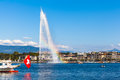 Water jet fountain with rainbow in geneva beautiful view of the the lake of and the cityscape of at sunset switzerland Royalty Free Stock Images