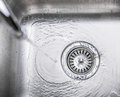 Water in kitchen sink viii flowing down the hole a Royalty Free Stock Photo