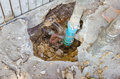 Water leaks from underground blue pipes Royalty Free Stock Photo