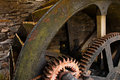Water mill wheel workings enclosed with ancient metal and wooden cog system part of industrial heritage Stock Photos