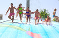 Water park rhodes greece faliraki august cheerful group of young people jumping on the wet bubble in the wet bubble is one of many Stock Photo