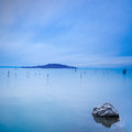Water, poles, island and rock in a blue morning on lake. Hills on background Stock Photo