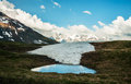 Water pond on the top of the mountain view on the snowy mountain range caucasus Royalty Free Stock Photography