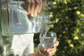 Water pouring glass in a hand of woman and from an old bottle outdoor shot blurred background with focus on the glass and Royalty Free Stock Photos