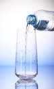 Water pouring from plastic bottle into empty drinking glass Royalty Free Stock Photo