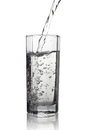 Water pouring into a tall glass with its reflection, closeup vie Royalty Free Stock Photo