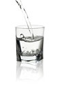 Water pouring into transparent glass with its reflection isolate Royalty Free Stock Photo