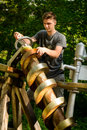 Water pump young man pumping with spiral archimedean Royalty Free Stock Photos