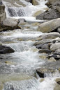 Water in a river with rocks the is flowing rocky plenty of stones and Stock Photos