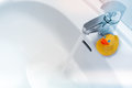 Water running from a faucet into a white sink with a rubber duck Royalty Free Stock Photo