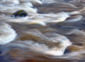 Water rushing boulder in a river Royalty Free Stock Photo