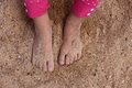Water on sand close up view of a toddlers feet covered in Royalty Free Stock Image